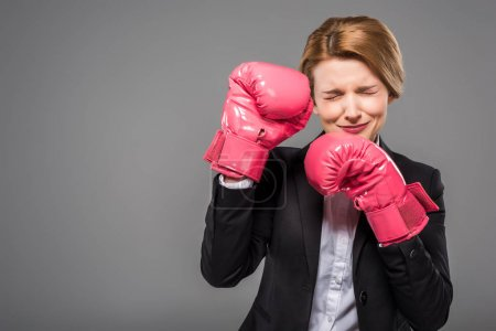 stressed businesswoman in suit and pink boxing gloves, isolated on grey