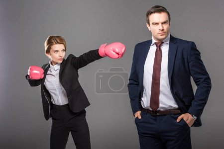 confident businesswoman in boxing gloves and handsome businessman, isolated on grey, feminism concept