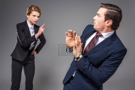 aggressive businesswoman quarreling and pointing at scared businessman, isolated on grey
