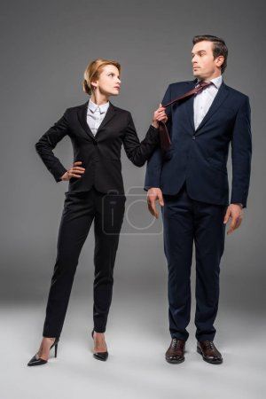 Photo for Aggressive female leader holding tie of businessman, isolated on grey - Royalty Free Image
