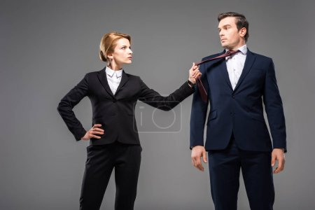 aggressive businesswoman holding tie of businessman, isolated on grey