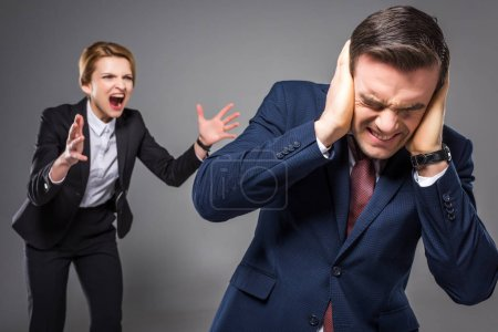aggressive female boss yelling at frightened businessman, isolated on grey