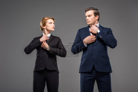 serious businesswoman and businessman fixing ties and looking at each other, isolated on grey, feminism concept