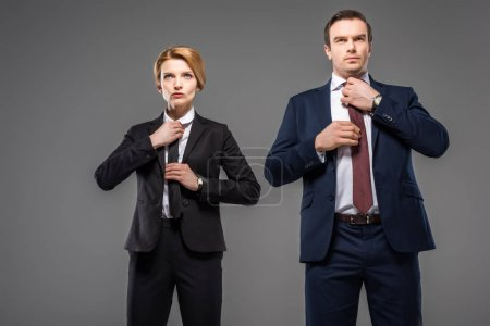 businesswoman and businessman fixing ties, isolated on grey, leader concept