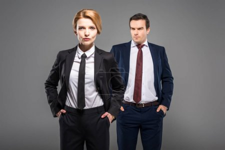 confident businesswoman and businessman in suits standing with hands in pockets, isolated on grey