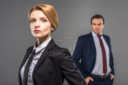 confident businesswoman and businessman standing behind, isolated on grey, feminism concept