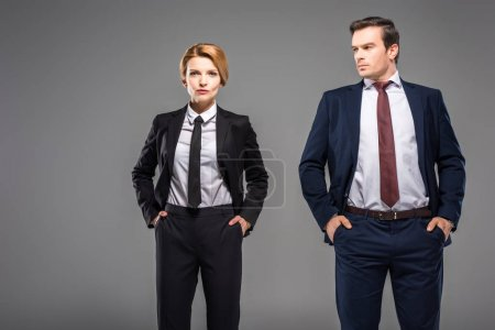 serious businesswoman and businessman posing with hands in pockets, isolated on grey