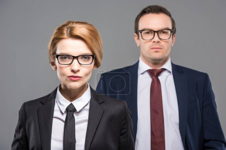 confident businesswoman and businessman in formal wear, isolated on grey