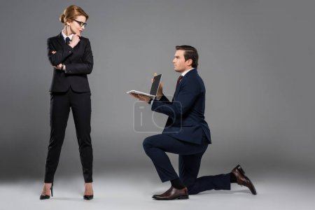businessman on one knee holding laptop for feminist businesswoman, isolated on grey