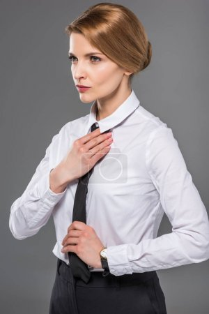 confident businesswoman wearing black tie, isolated on grey