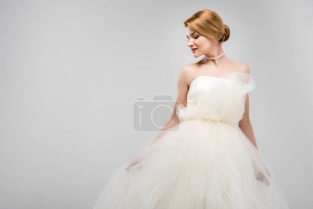 attractive bride posing in white wedding dress, isolated on grey