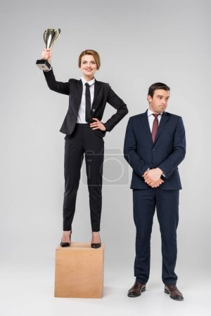 happy businesswoman with trophy cup standing on podium, upset colleague standing near, isolated on grey