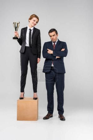 happy businesswoman with trophy cup standing on podium, upset businessman standing near, isolated on grey