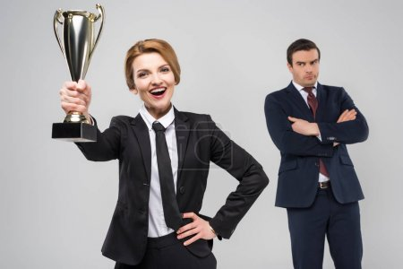 Photo for Excited businesswoman with award and upset businessman behind, isolated on grey - Royalty Free Image