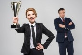 excited businesswoman with award and upset businessman behind, isolated on grey