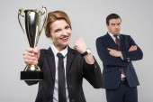 excited businesswoman with trophy cup and upset businessman behind, isolated on grey