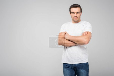 handsome man with crossed arms looking at camera, isolated on grey