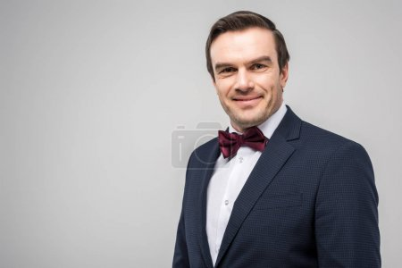 happy groom in tuxedo and bow tie, isolated on grey