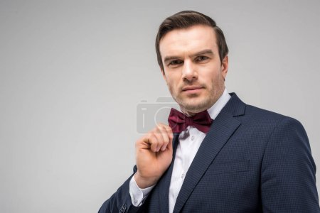 portrait of handsome man posing in festive bow tie, isolated on grey