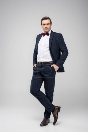 handsome man posing in tuxedo with hands in pockets, isolated on grey