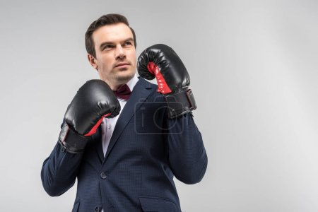 handsome thoughtful man in suit and bow tie wearing boxing gloves, isolated on grey