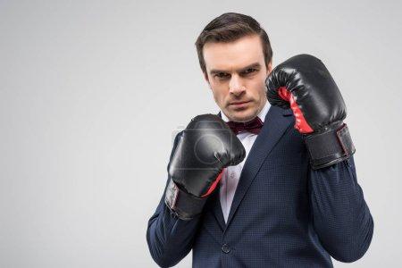 Photo pour Bel homme en smoking et gants de boxe, isolé sur gris - image libre de droit