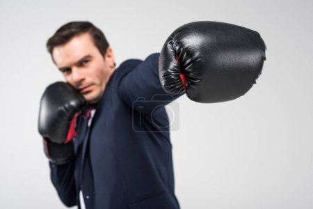 selective focus of serious man in boxing gloves, isolated on grey