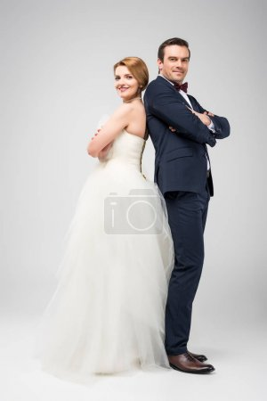 Photo for Wedding couple standing back to back with crossed arms, isolated on grey - Royalty Free Image