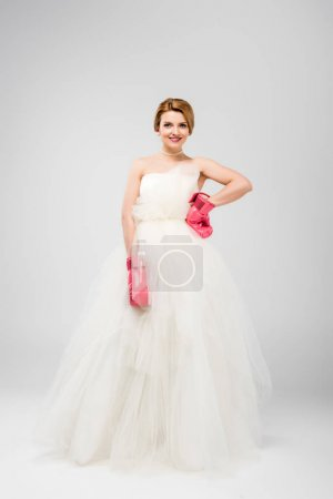 smiling bride in white wedding dress and boxing gloves, isolated on grey, feminism concept
