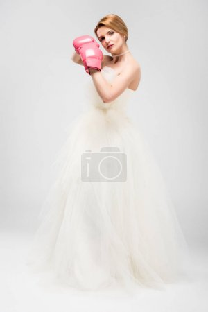 bride in white wedding dress and boxing gloves, isolated on grey, feminism concept