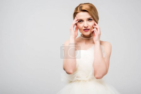 portrait of attractive tender bride in white wedding dress, isolated on grey