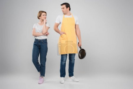 happy wife and husband in apron with frying pan, feminism concept, isolated on grey