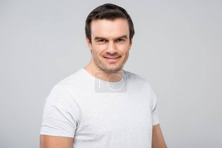 portrait of handsome man smiling at camera, isolated on grey