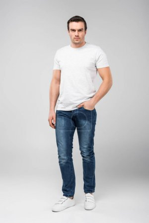 Photo for Handsome man with hand in pocket looking at camera, isolated on grey - Royalty Free Image