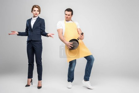 businesswoman gesturing while male householder playing on frying pan like on guitar, isolated on grey