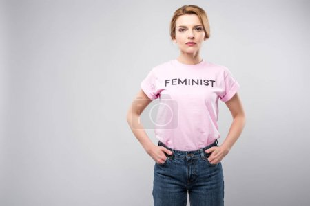 woman in pink feminist t-shirt posing with hands in pockets, isolated on grey