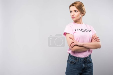 woman in pink feminist t-shirt posing with crossed arms, isolated on grey