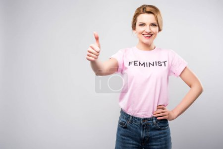 smiling woman in pink feminist t-shirt showing thumb up, isolated on grey