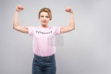 strong woman in pink feminist t-shirt showing muscles on arms, isolated on grey