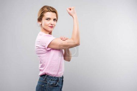 Photo pour Femme féministe en t-shirt rose montrant les muscles, isolé sur gris - image libre de droit