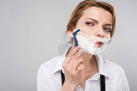 businesswoman shaving face her face, isolated on grey, feminism concept