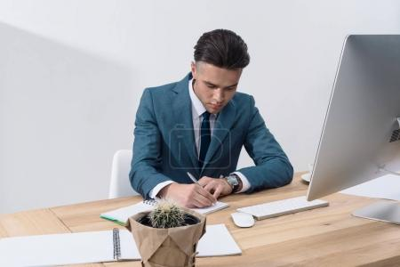 Photo for Concentrated young businessman writing in notebook while working at table with desktop computer - Royalty Free Image
