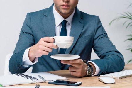 Photo pour Coupé coup de jeune homme d'affaires élégant en costume tenant tasse de café et soucoupe - image libre de droit