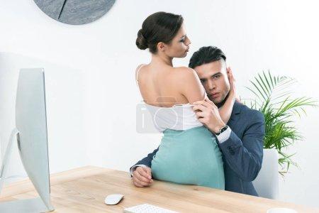 Foto de Joven pareja apasionada de empresarios abrazándose en los juegos previos en el lugar de trabajo en la oficina - Imagen libre de derechos