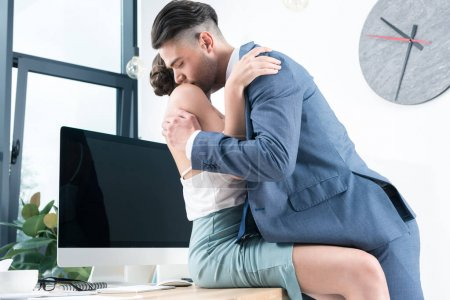 business colleagues kissing in foreplay at workplace