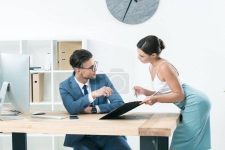 Photo for Young charming secretary talking to her boss at office - Royalty Free Image