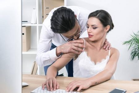 businessman kissing colleague during work