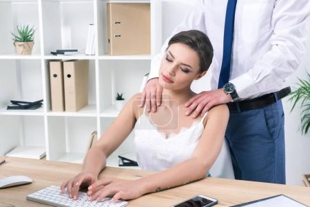 businesswoman enjoying massage from colleague at workplace
