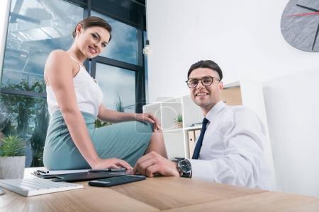 Foto de Jóvenes empresarios sonrientes mirando a la cámara mientras están sentados en el lugar de trabajo en la oficina - Imagen libre de derechos