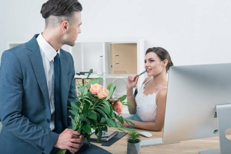 businessman presenting roses to colleague at workplace
